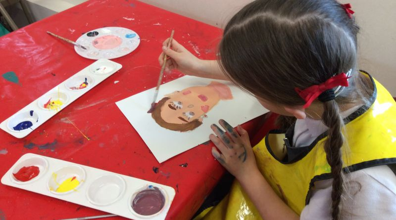 Young girl painting a portrait