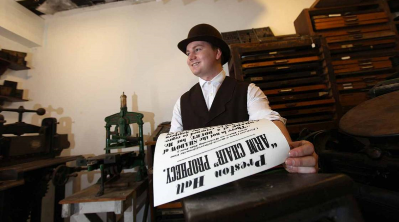 A male volunteer in Victorian clothing working a printing press at preston park museum and grounds