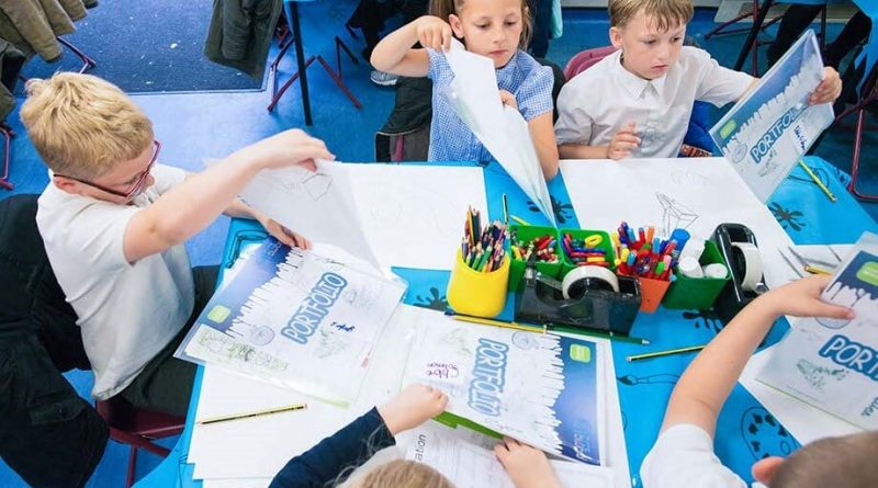 A group of school children sit around a table ready to take part in Arts Award Discover