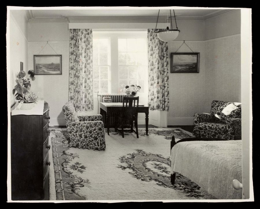 Interior of a bedroom in ticehurst hospital, showing a chair next to a window and table and the end corner of a bed showing on the right