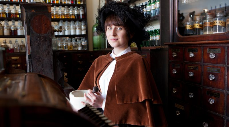 a woman stands in a Victorian chemist