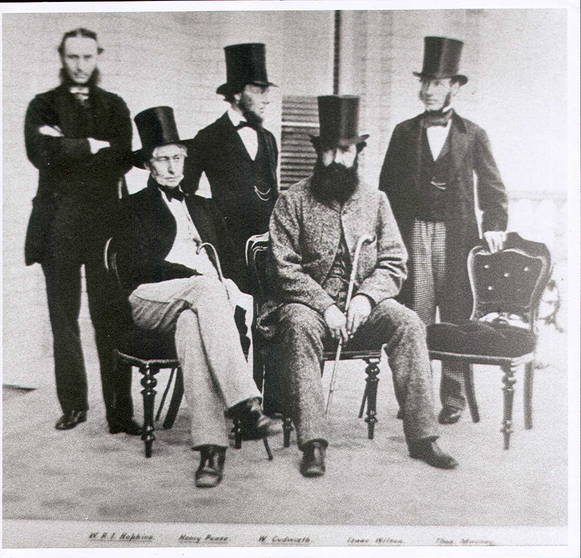 a group of men in top hats pose for a photograph