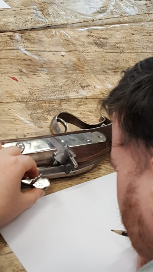 Man from Socialites closely examining the trigger and lock of a musket