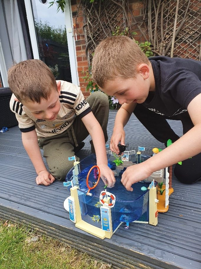 two boy playing together with a blue lego style toy in their garden