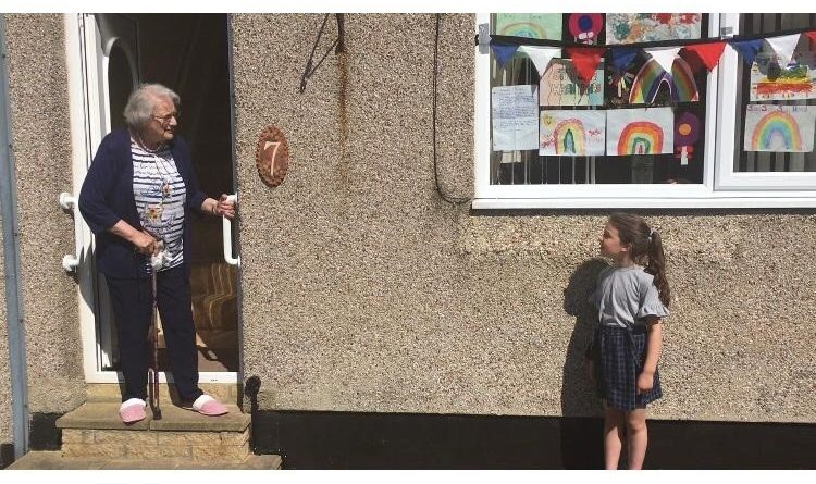 A little girl stands a short distance away from an elderly woman at her front door. They are facing each other and talking. Grandmother and granddaughter
