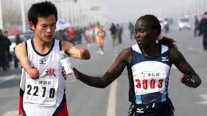 Two people are running in a race, one holds out a bottle of water for the other who is disabled