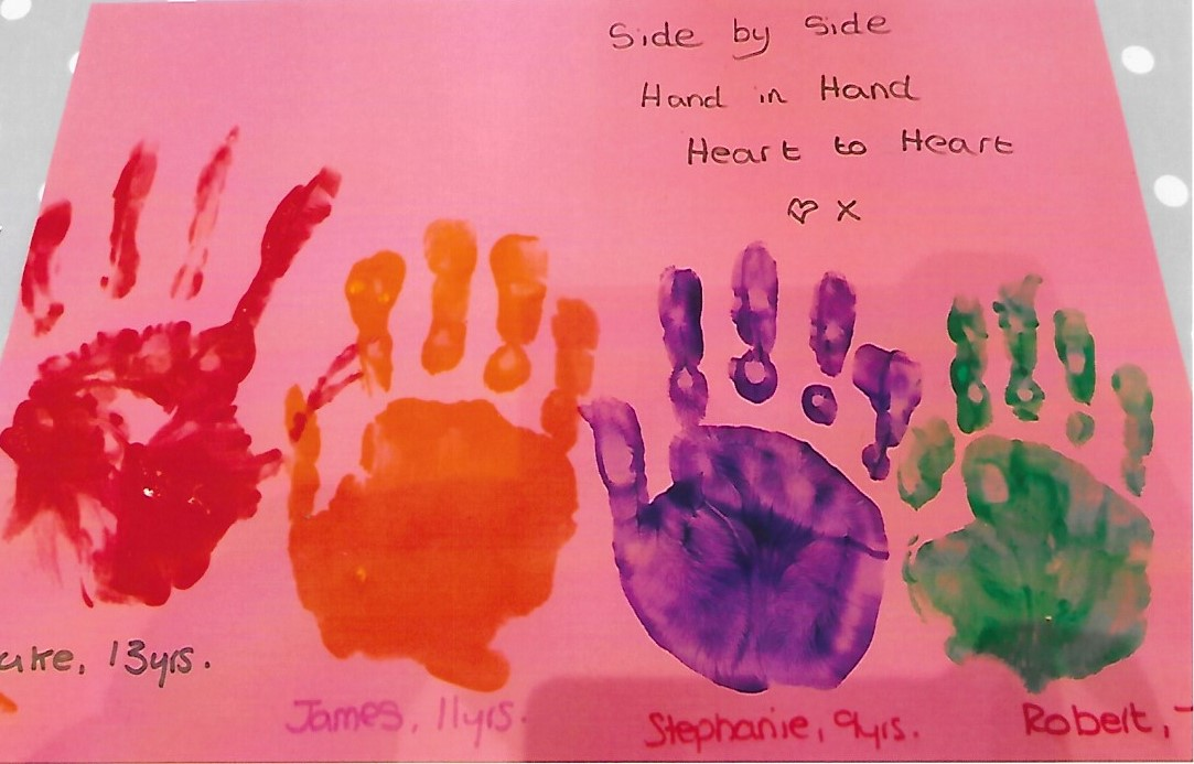 paint hand prints of two brothers on pink card