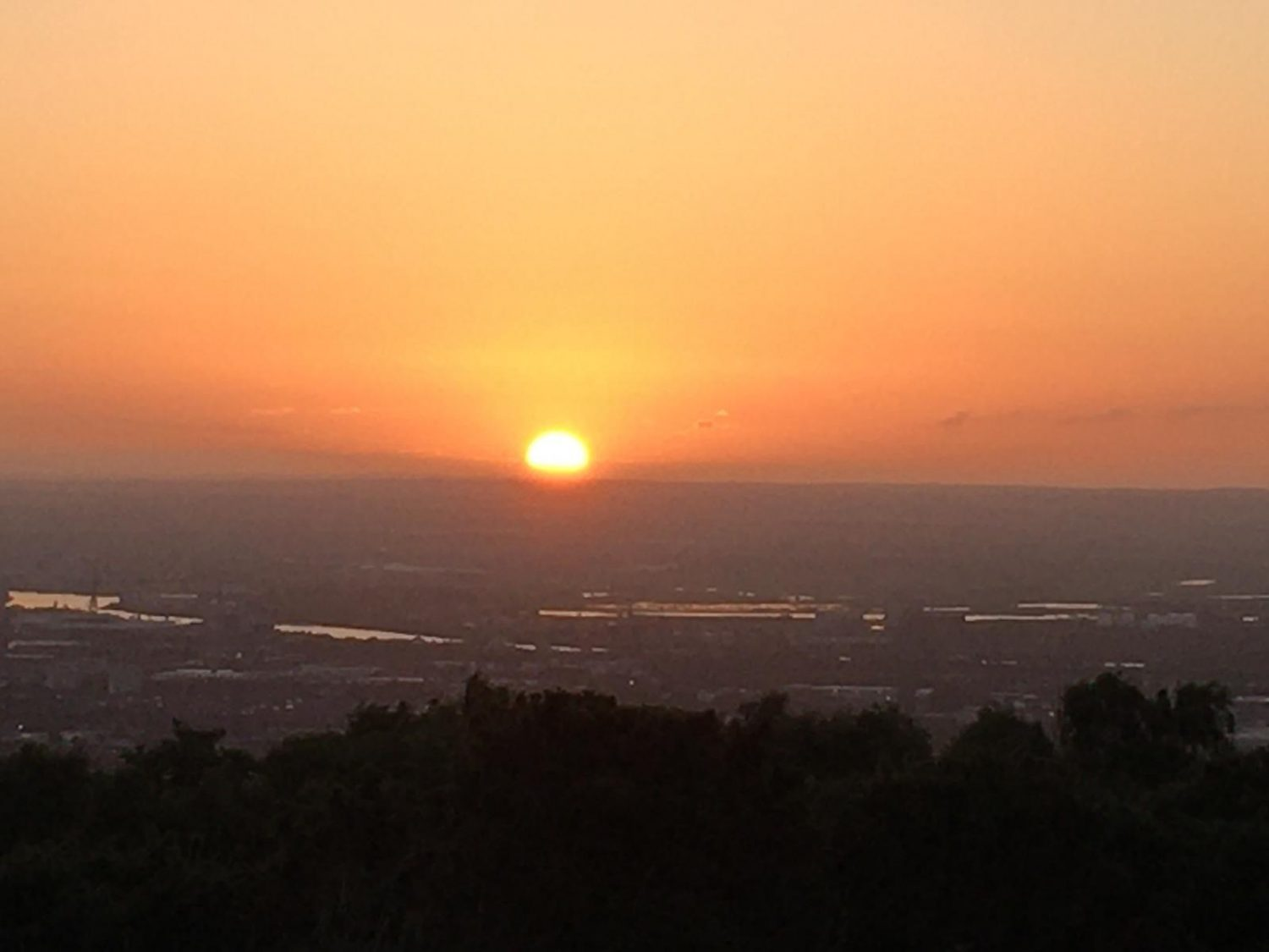 Sun setting over a built up landscape with a large hill i n the distance. The sky is pink, red, and yellow