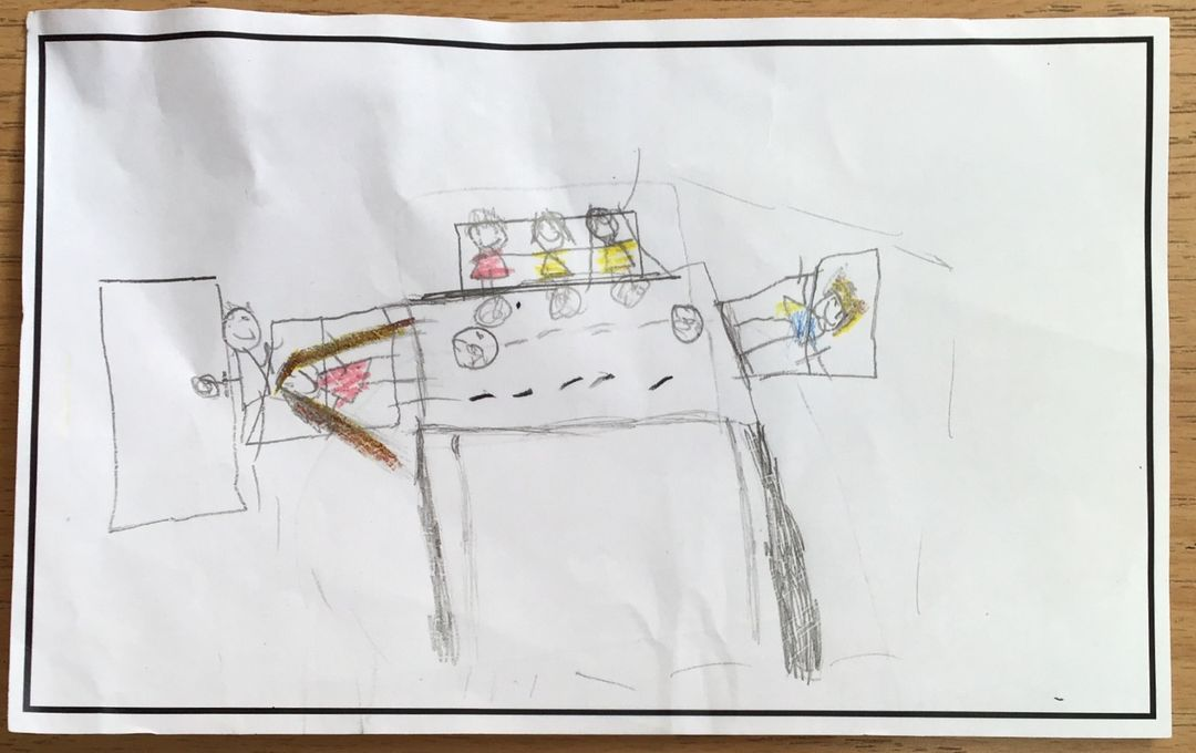 childrens drawing of a family eading dinner around the table