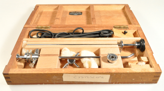 Open wooden case holding a thin silver medical tube and a black tube next to it