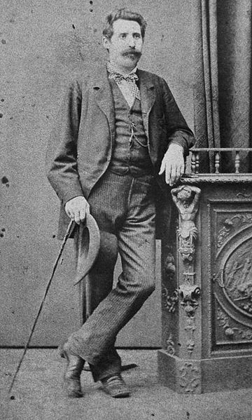photograph of a man in a three piece suite leaning on a side table with his hat and cane in his other hand.