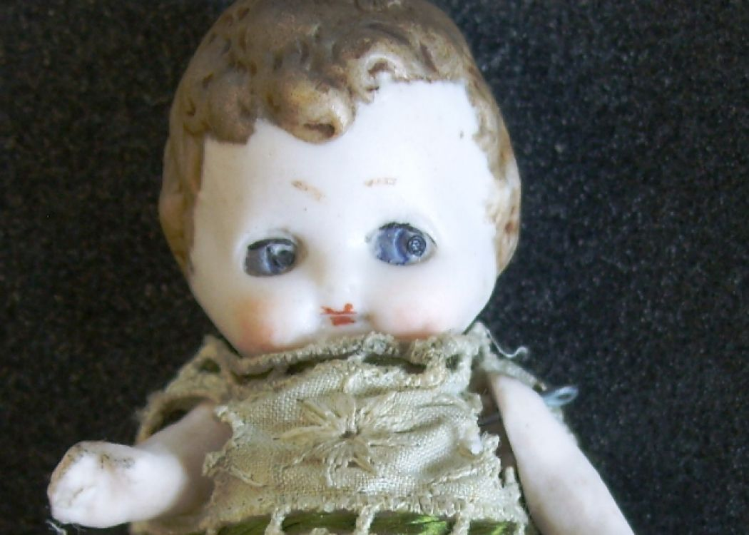 Small doll with large plain dress and a white face with big blue eyes.