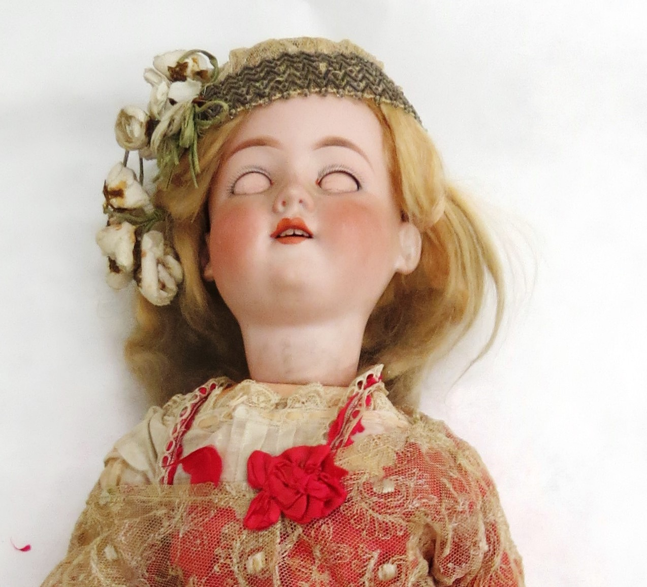 full length picture of a 1915 doll dressed like a flapper. Dressed in red with no eyes and white flowers in the hair