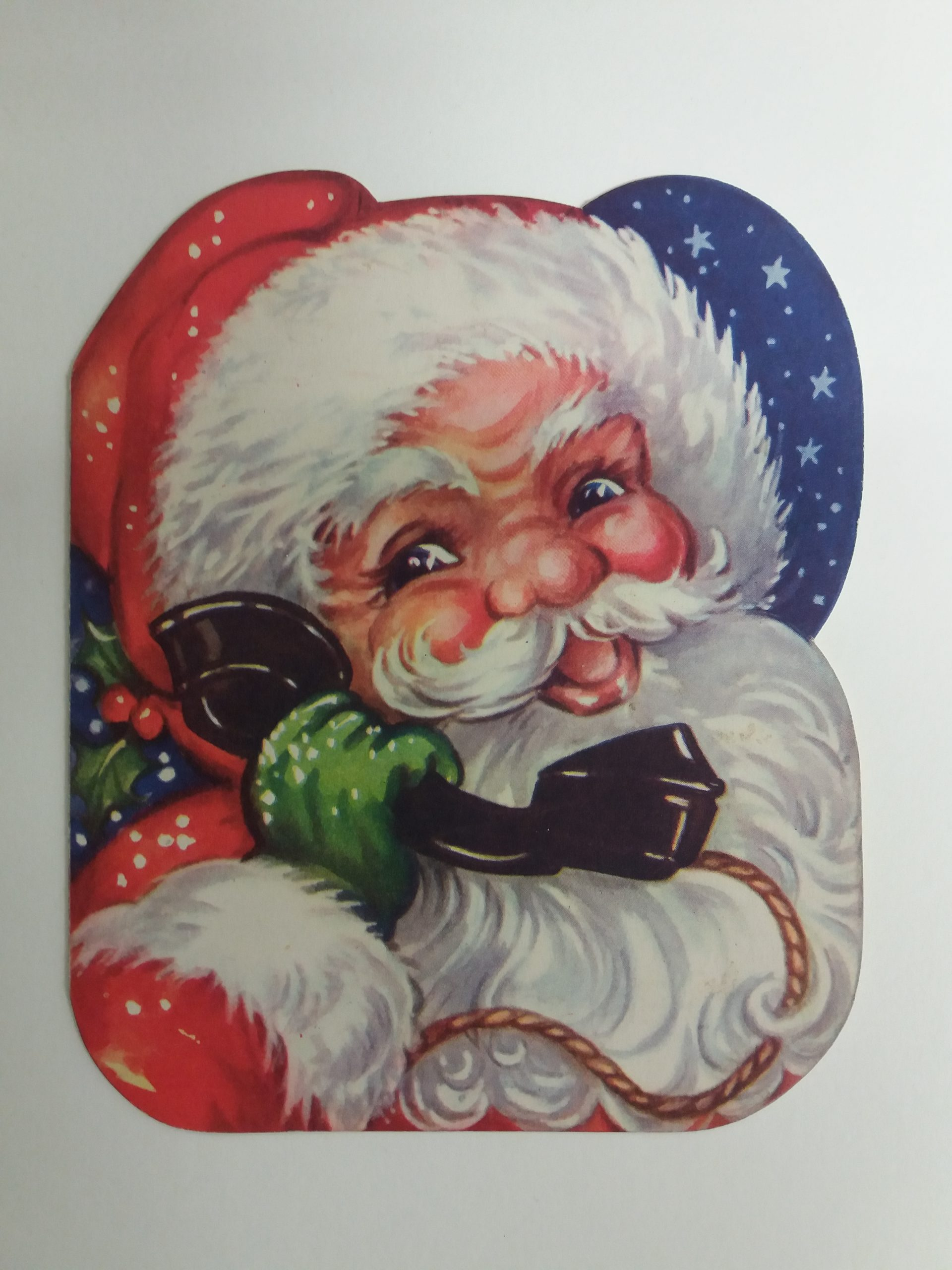 Colour image of Father Christmas holding an old style black telephone handset