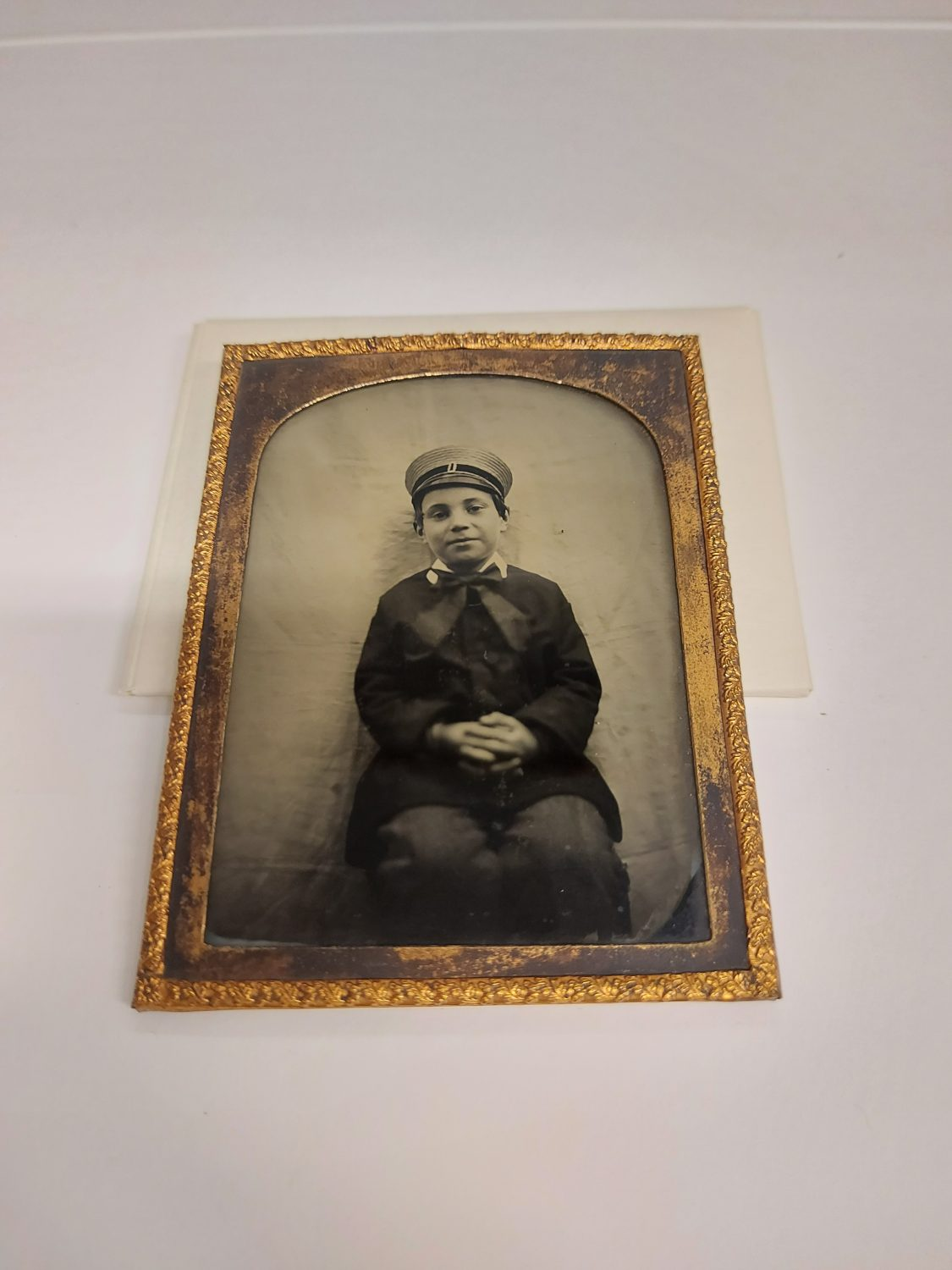 Ambrotype photograph of a young boy sitting with his hands clasped on his lap. Hes wearing a sailor type hat and suite. Photograph is black and white glass negative in gold frame