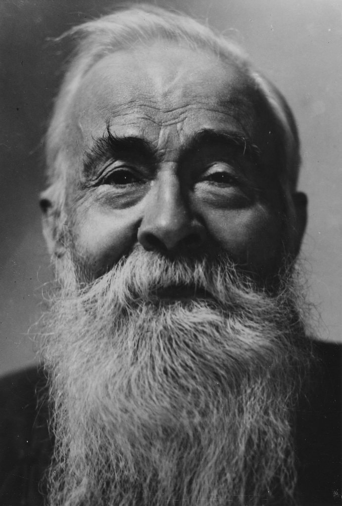 close up picture of the face of Edmund Backhouse, and old man with a large white beard and long eyebrows styled in an upward fashion. His face is sunken with deep lines on his brow, fresh plump cheeks and set back eyes.