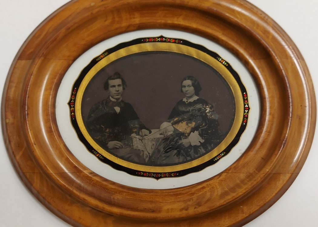 This oval shaped Ambrotype is quite large in comparison to the others and shows a young couple sitting side by side. Its framed in a deep wooden frame and looks as though it has been hung up on a wall.