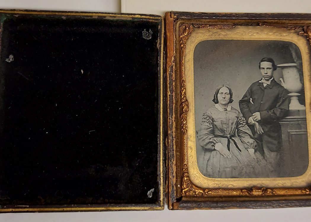 This Ambrotype shows a young couple with the woman sat down and the man stands next to her. The glass plate is in a gold frame and is encased in a leather bound safety case. Inside the case is finished in velvet.