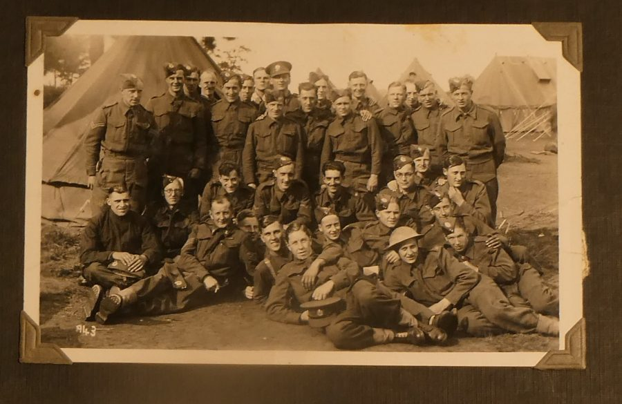 A large group of soldiers pose for a photograph. Some men lie on the floor whilst others stand at the back.