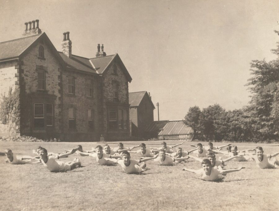 Black and white image of children exercising on the grass in front of Rosebank School Hartlepool