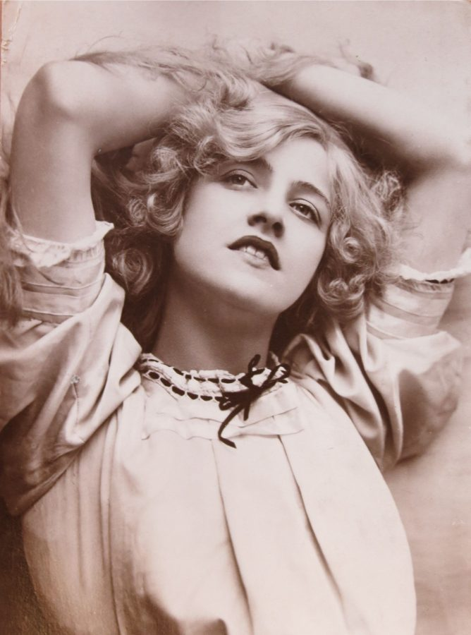 Postcard of Ivy Close with her arms above her head. Her short hair falls down her face in waves. Shes wearing a loose cut blouse with sleeves.
