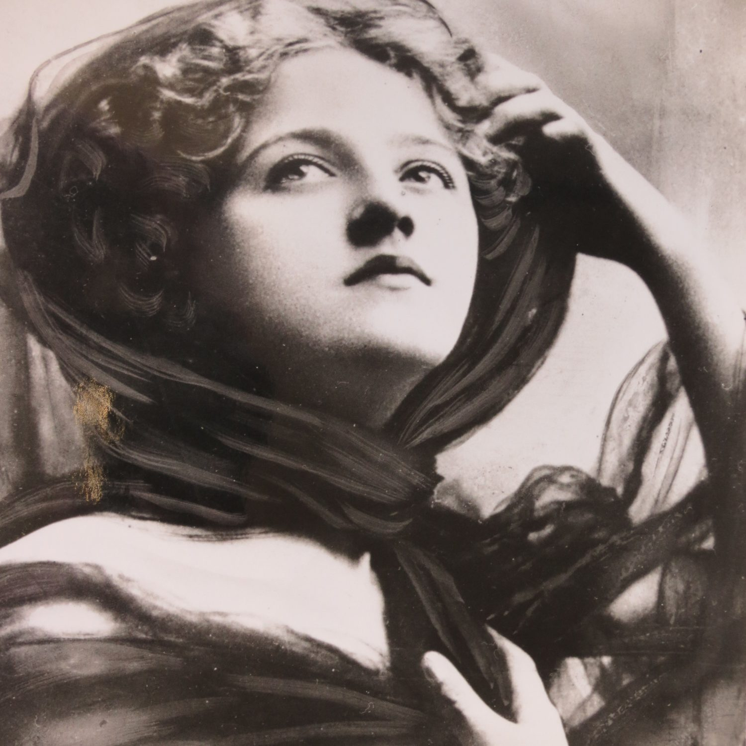 Head and shoulders picture of Ivy Close. She has a full face lit with light, looking upwards. She has a scarf over her full hairstyle coming down around her neck. She has her arms posed artistically with one on her head scarf the other on her chest