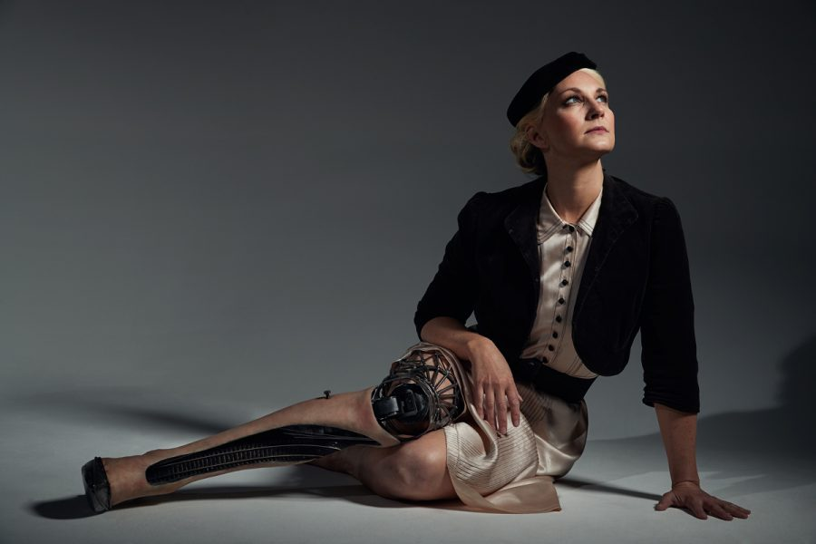 A woman sits on the floor looking up. She wears an artificial leg with a cut out on the shin where a model railway track sits. The top of the leg is welded in an art deco style.