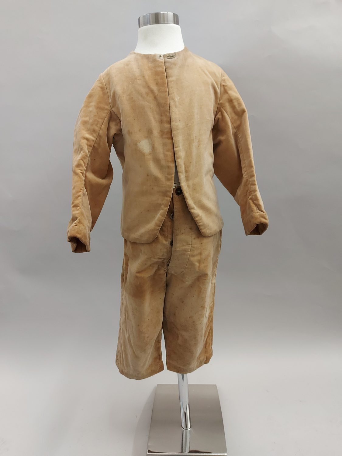 Boys suit on a mannequin, consisting of trousers and a jacket. The suit is a dull cream coloured crushed velvet speckled with lighter and darker spots due to age. The jacket has no buttons but a small fasting at the top.
