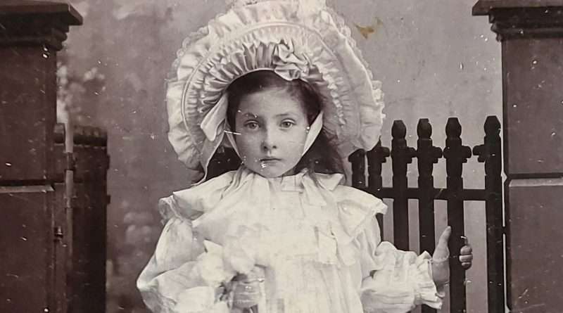 A little girl stands facing the camera with torso up in view. She is holding onto an iron gate with one hand and the other is on her waist. She is wearing a white ruffled dress with large collar and puffed sleeves at the wrist. Her dark hair goes behind her back and she wears a large white bonnet turned upwards with layers of ruffles.
