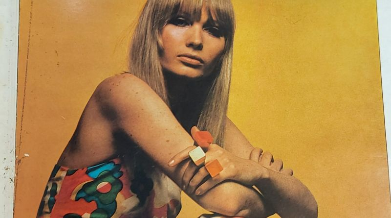 Front cover of a magazine. It has a white border with a large colorful photograph of a model sat down. It has an orange background and the model is sitting on the floor with her elbows on her knees. she has straight hair, dark eye make up, a natural lipstick and she is wearing a colorful flower print jump suit.