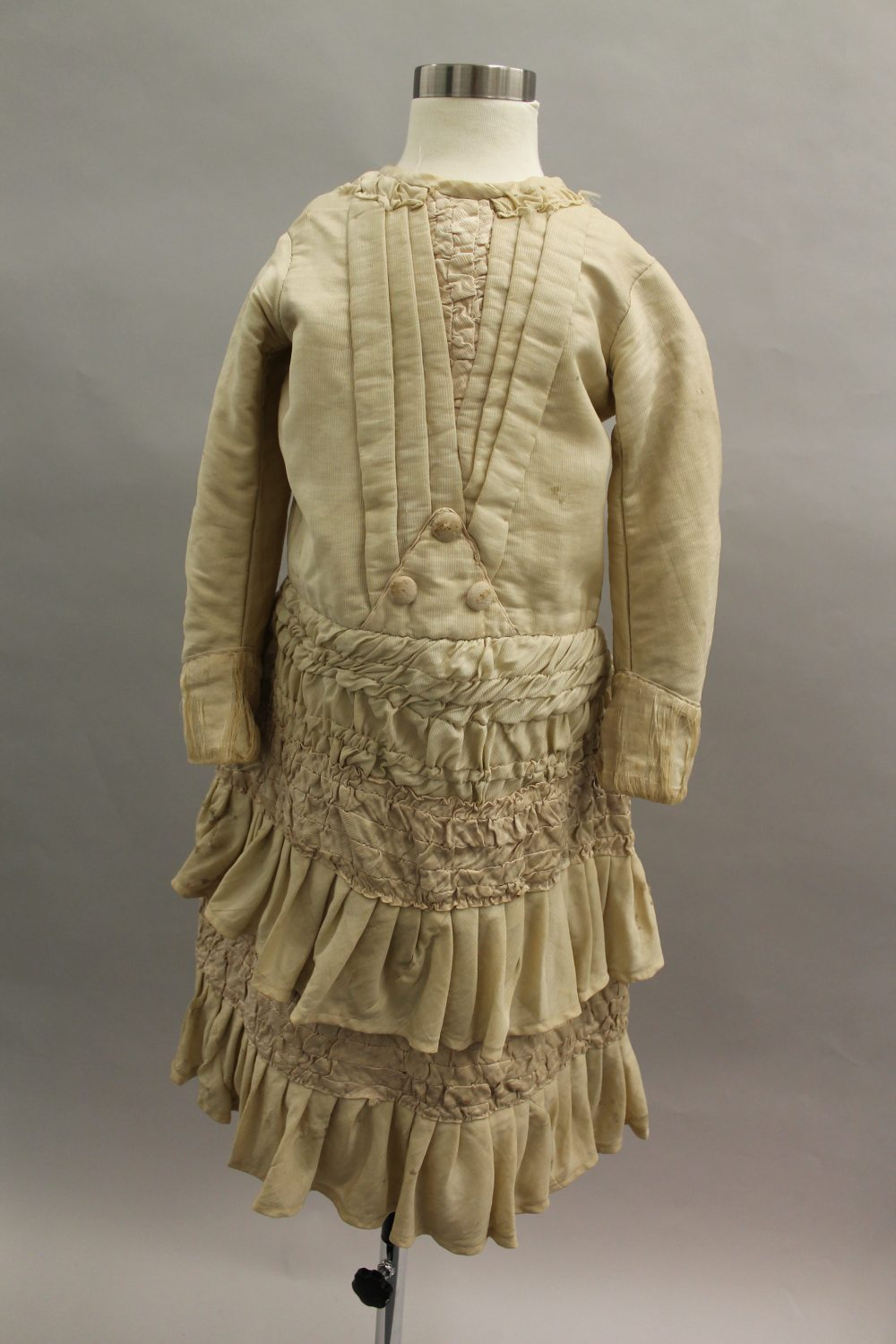 Girls cream coloured dress. The bodice has sewn detail going down the front into a point and the skirt features flounces. The back features a small bustle mimicking the fashionable style of women at the time, 1880s.
