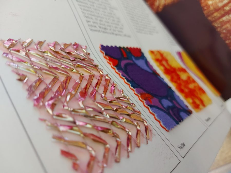 Fabric swatches in a white magazine. The swatch in focus shows a see through material with sewn pink shiny beads on in a zig zag pattern.