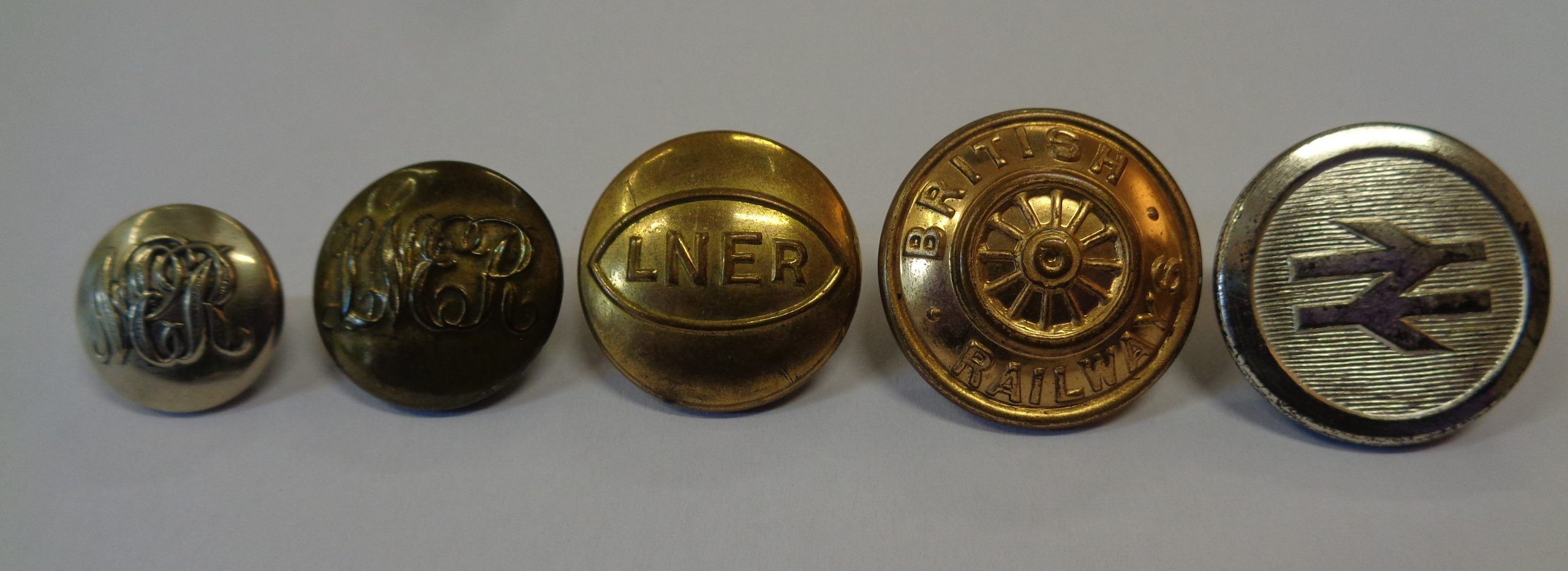 picture showing the evolution of railway uniform buttons. Starting with small gold ones with NER scrawled over them, to larger NER buttons, then to a clear brass button with LNER embossed on and finally the old and new style British Railway buttons