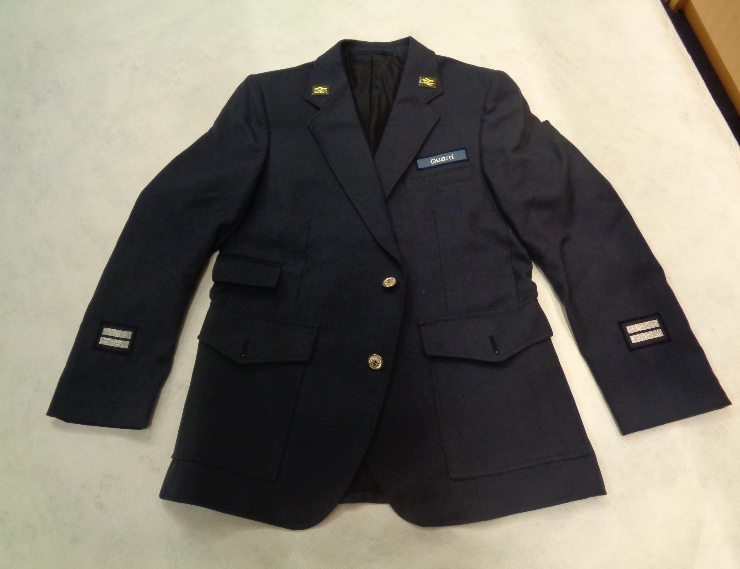 British Railway uniform jacket in deep navy with lapels laid out.