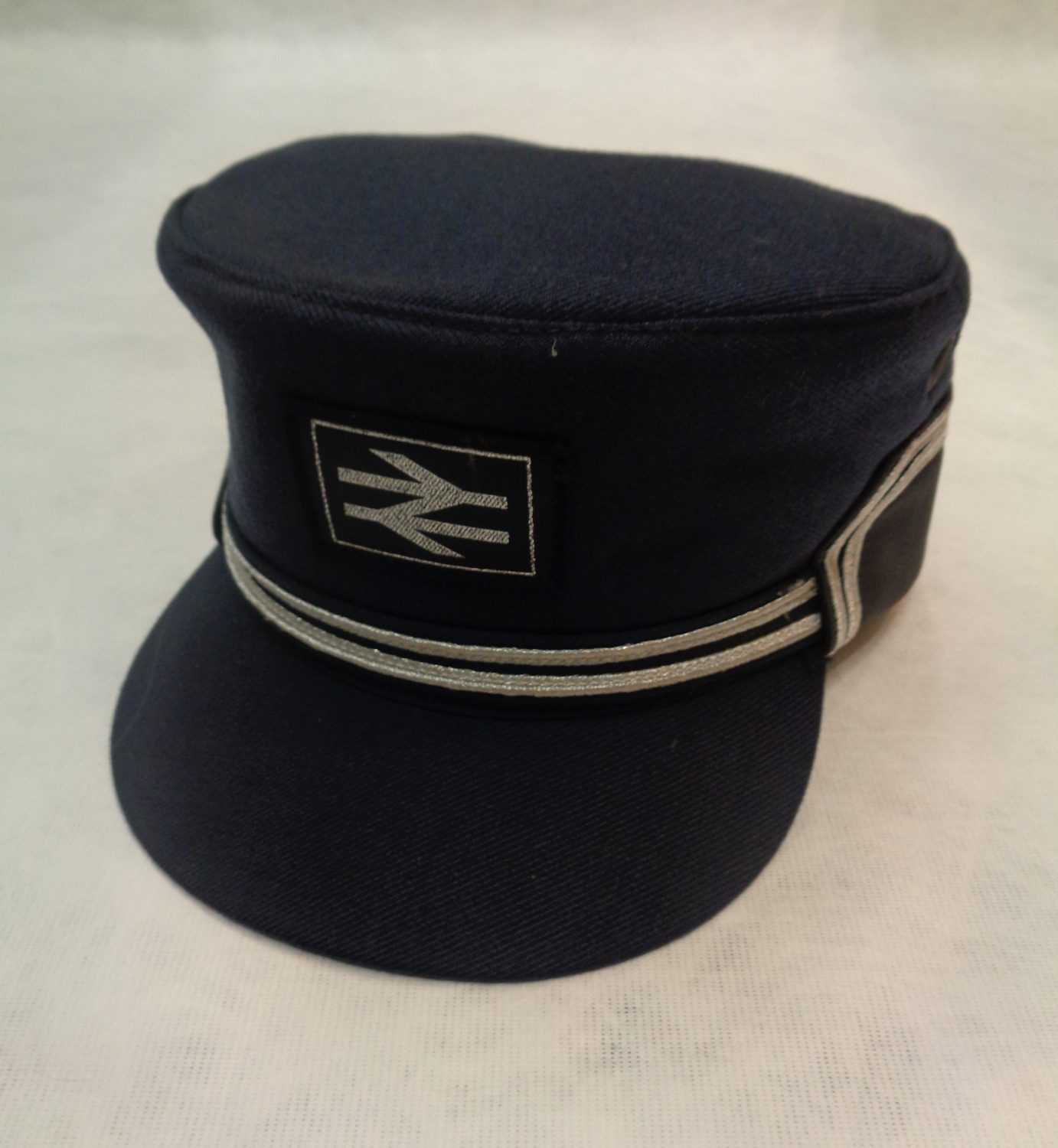 Box structured cap in navy with two silver bands and the new British railways logo on the front also in silver.